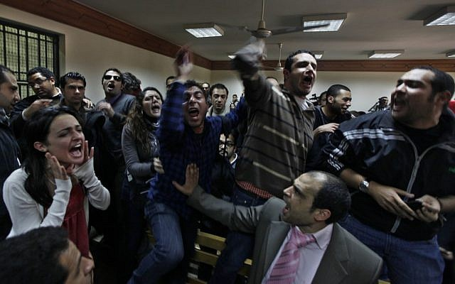 Egyptian protesters during a trial of employees of pro-democracy groups charged with using foreign funds to foment unrest in Cairo. The US may approve funding for Egypt despite its lack of pro-democracy reform. (photo credit: AP/Khalil Hamra)