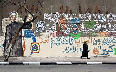 "An Egyptian woman walks past a mural with a picture depicting a victim of clashes between protesters and army soldiers in December 2011, with verses of Quran that read in Arabic ""God, we obeyed our lords and they misled us, punish them God twice as much and curse them"" in Cairo, Egypt. (photo credit: AP Photo/Nasser Nasser)"