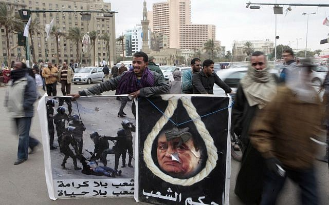 """Liberals and Islamists are at the center of a constitutional crisis in Egypt. The protester on the left holds a sign that reads """"A nation without dignity is a nation without life."""" (photo credit: AP/Amr Nabil)"""