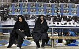 Iranian women surrounded by campaign posters at a bus stop, March 1, 2012 (photo credit: AP Photo/Vahid Salemi)
