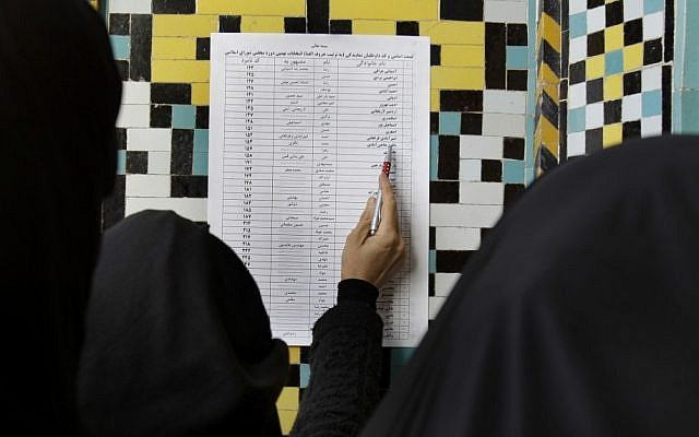 An Iranian woman looks at the list of the candidates for the parliamentary elections at Masoumeh shrine in the city of Qom in March, 2012. (photo credit: AP)