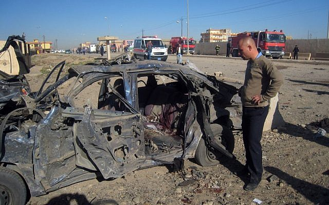 A man stands next to a destroyed vehicle at the scene of a car bomb attack in Kirkuk, 290 kilometers (180 miles) north of Baghdad (photo credit: AP/Emad Matti)