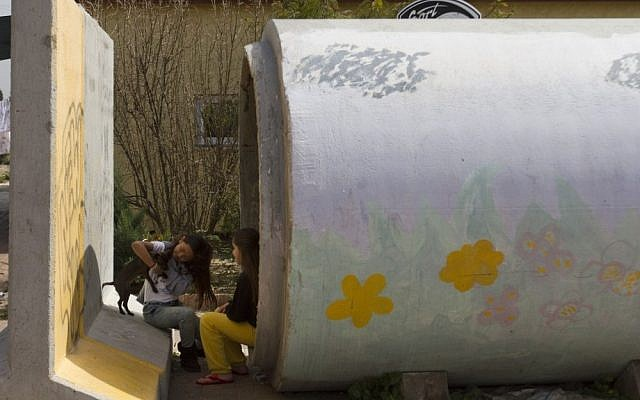 Israeli children play outside a sewage pipe which is ready to be used as a protective shelter in Nitzan, near Ashdod, Sunday. (photo credit: AP)
