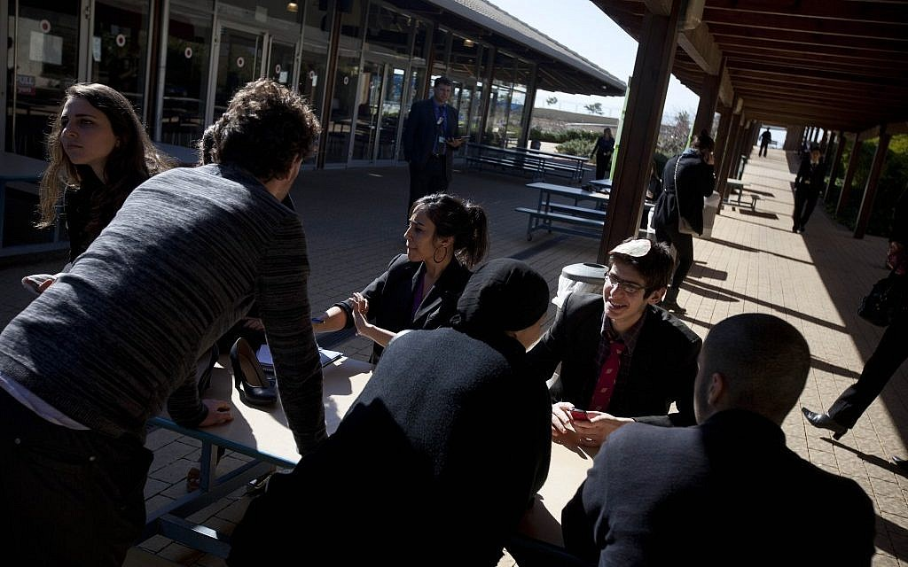 Students sit together during model United Nations 'peace negotiations' at the American International school in Even Yehuda. (photo credit: AP/Oded Balilty)