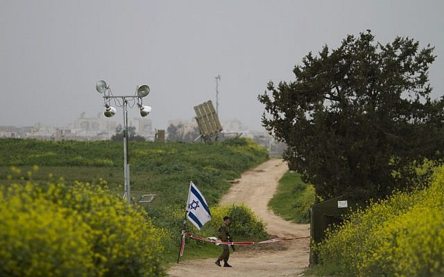 A soldier stands guard next to an Iron Dome battery near Ashdod (photo credit: AP/Ariel Schalit)