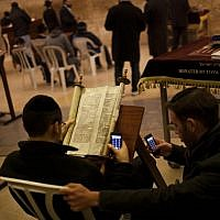 Two Jewish men check their smart phones as they read a religious scroll at the Western Wall, the holiest site where Jews pray, in Jerusalem's Old City. (photo credit: AP/Bernat Armangue)