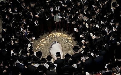 Ultra-Orthodox mourners surround the body of Rabbi Moshe Yehoshua Hager at his funeral in Bnei Brak on Wednesday. (photo credit: AP/Oded Balilty)