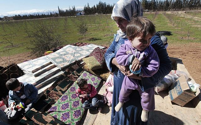 Syrian refugees by the Lebanese border (photo credit: AP/Hussein Malla)