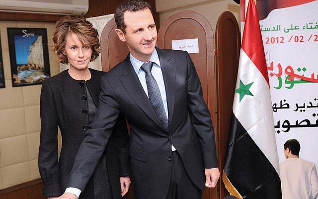Syrian President Bashar Assad casts his ballot next to his wife Asma at a polling station during a referendum last year on a new constitution, in Damascus. (photo credit: AP Photo/SANA, File)