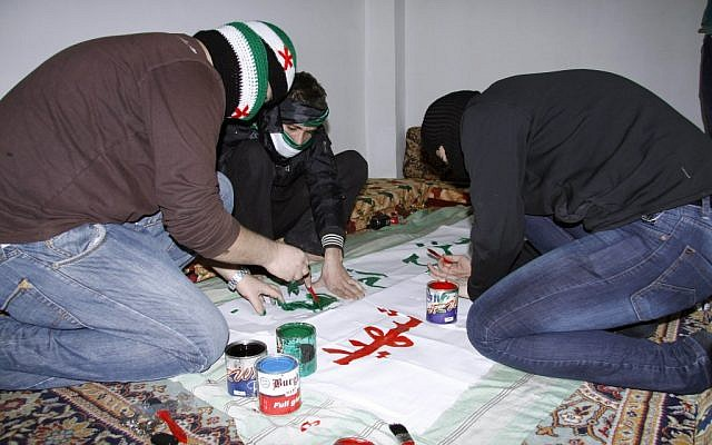 Anti-Syrian regime activists cover their faces with scarves in the colors of the Syrian revolution flag as they prepare a banner to be held in a protest. (illustrative photo; photo credit: AP)