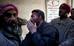 An injured man arrives at hospital in Syria (photo credit: AP Photo/Rodrigo Abd)