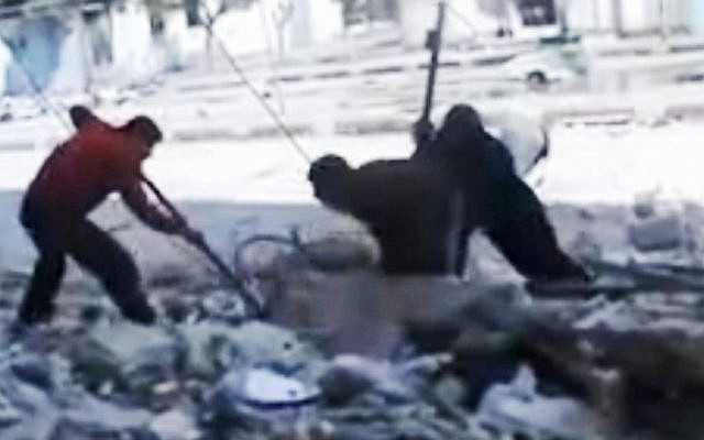 This screen capture, taken from an amateur video in Homs, shows Syrians pulling out a man's body from the rubble of a building after it was bombed last week. (photo credit: Syria Media Center via APTN/AP)