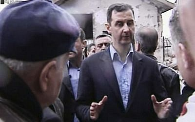 Syrian President Bashar Assad visits the Baba Amr neighborhood in Homs, Syria, on Tuesday. (photo credit: AP/Syrian State Television)