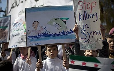 Children hold anti government posters during a protest in a town in north Syria. (photo credit: AP)
