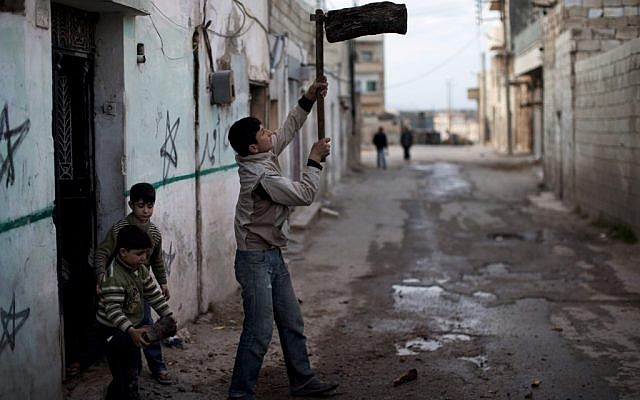 A boy chopping wood in Idlib, Syria (photo credit: AP/Rodrigo Abd)