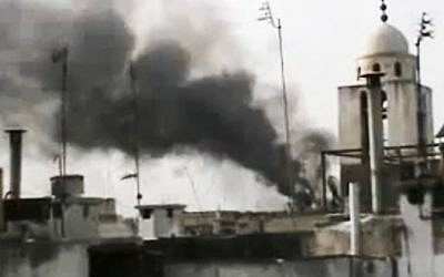 This image made from amateur video and released by Shaam News Network Monday, March 26, 2012, purports to show smoke rising from buildings in Homs, Syria (photo credit: AP/Shaam News Network via APTN)