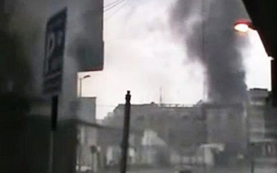 File: A screen capture from amateur video purporting to show black smoke rising from buildings that were fired upon in Homs. Syrian President Bashar Assad says he will spare no effort to make the mission of UN-Arab League envoy Kofi Annan a success but he demands that armed opponents commit to halting violence. (photo credit: Syria Media Center via APTN/AP)