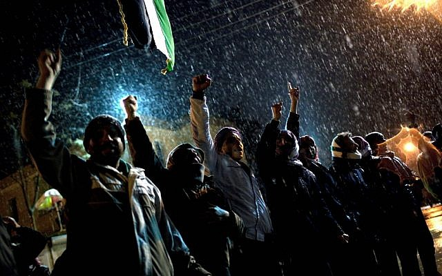 Free Syrian Army supporters chant anti government slogans under snowfall on the outskirts of Idlib , north Syria, on Wednesday (photo credit: AP Photo/Rodrigo Abd)