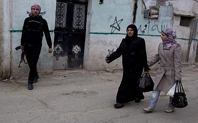 Syrian women walk by a member of the Free Syrian Army in Idlib on Monday (photo credit: Rodrigo Abd/AP)