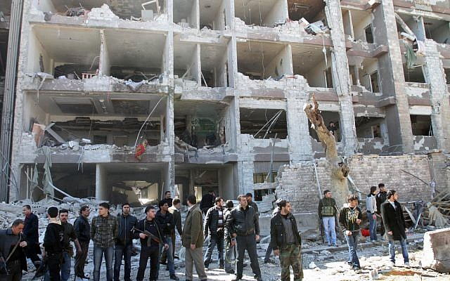 Syrian security officers in front of the damaged building of the aviation intelligence department, which was attacked by one of two explosions in Damascus on Saturday (photo credit: AP/Bassem Tellawi)