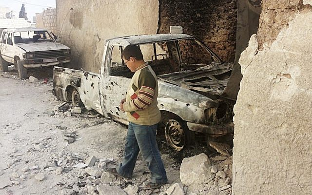 A boy examines cars damaged in an attack from Syrian government forces shelling at Sarmeen town in northern Syria. (photo credit: Edlib News Network/AP)