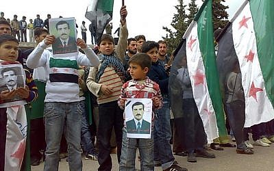 A citizen journalism image of anti-Syrian regime protesters in Idlib, near the Syrian-Turkish border, Friday, holding posters of a man allegedly killed by pro-Syrian forces and raising the Syrian flag. (photo credit: AP/Edlib News Network)