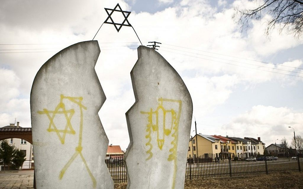 A monument at a Jewish cemetery in Wysokie Mazowieckie, Poland is found desecrated with anti-Semitic graffiti, March 2012 (Jedrzej Wojnar/AP)