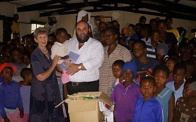 Ruth Feigenbaum, Traveling Rabbi Moshe Silberhaft and Patricia Tshabalala in the library for Aids orphans in Bulawayo (Photo credit: JTA)