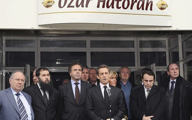 French President Nicolas Sarkozy, center, speaks in front of the Ozar Hatorah Jewish school in Toulouse, following a deadly shooting there on Monday morning. (photo credit: Eric Cabanis/AP)