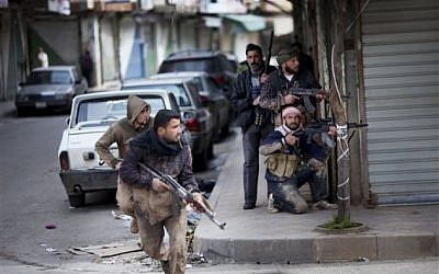 Syrian rebels take position during clashes with government forces in Idlib, north Syria. (photo credit: AP)