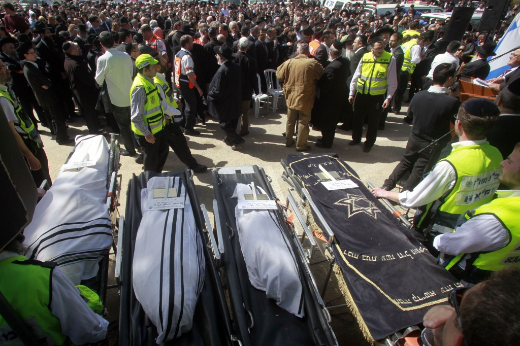 The bodies of the Toulouse Jewish school shooting victims, shrouded in talitot, prior to burial at the Givat Shaul cemetery in Jerusalem on Wednesday. (photo credit: Uri Lenz/Flash 90)