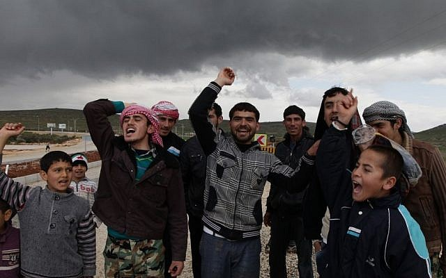 Newly arrived Syrian refugees, who fled the violence in their country, demonstrate at the border in Reyhanli, Turkey in March. (photo credit: AP)
