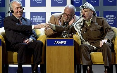 Yasser Arafat shakes hands with Shimon Peres at the World Economic Forum in Davos, 2001 (photo credit: CC BY-SA World Economic Forum)