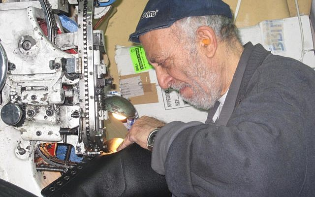 Yosef Yehezkia, at the Brill factory in Rishon Lezion, punches eyelets into boot leather (photo credit: Mitch Ginsburg/Times of Israel)