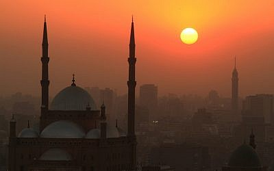 The sun sets over a mosque. (photo credit: Wissam Nassar/Flash90)