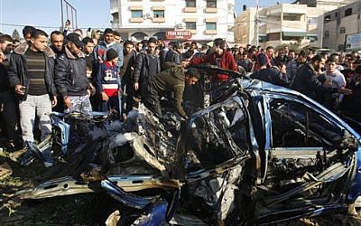 Palestinians gather around the wreckage of Zuhair al-Qaissi's car, targeted in an Israeli airstrike in Gaza City, Friday. (photo credit: AP photo/Hatem Moussa)