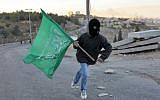 A Jerusalem youth carries the Hamas flag (Nati Shohat/Flash90)