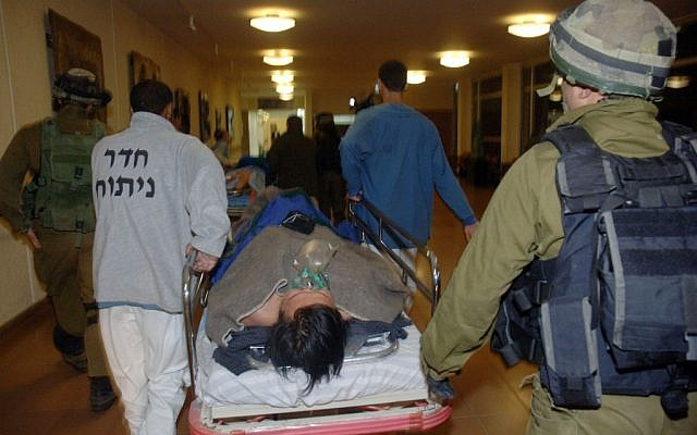 Thai workers, injured when rockets fired from Gaza into southern Israel hit the area of Eshkol, are brought into the Soroka hospital late Friday night. (photo credit: Dudu Greenspan/Flash90)