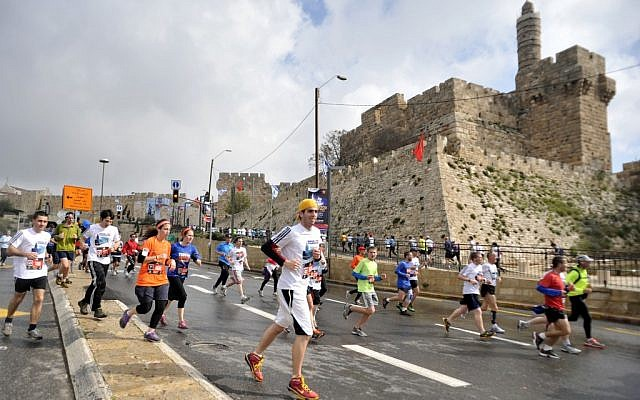 Runners sloshing by the Old City in the 2012 Jerusalem Marathon. (photo credit: Yoav Ari Dudkevitch/ Flash90)