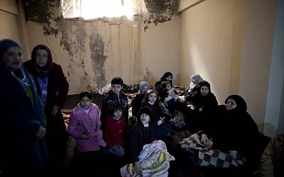 Syrian women and children take shelter from fierce fighting between the Free Syrian Army and government troops in Idlib, north Syria (photo credit:AP/Rodrigo Abd)