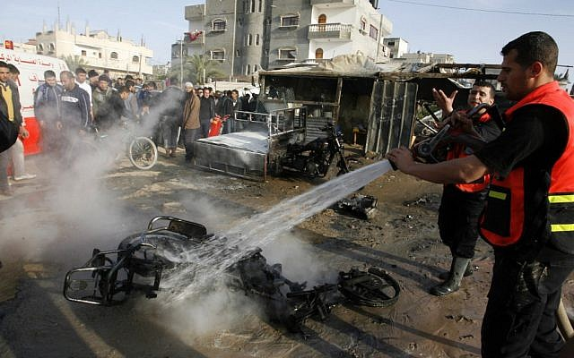 A Palestinian tries to extinguish a fire after an Israeli airstrike in Rafah, southern Gaza Strip, in 2012. (photo credit: Abed Rahim Khatib/Flash90)