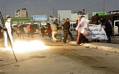 Activists run away from a stun grenade fired by Israeli troops to disperse a rally marking International Women's Day and calling for the release of Palestinian prisoner Hana Shalabi, at the Kalandia checkpoint between Jerusalem and Ramallah, on Thursday. (photo credit: AP/Majjdi Mohammed)