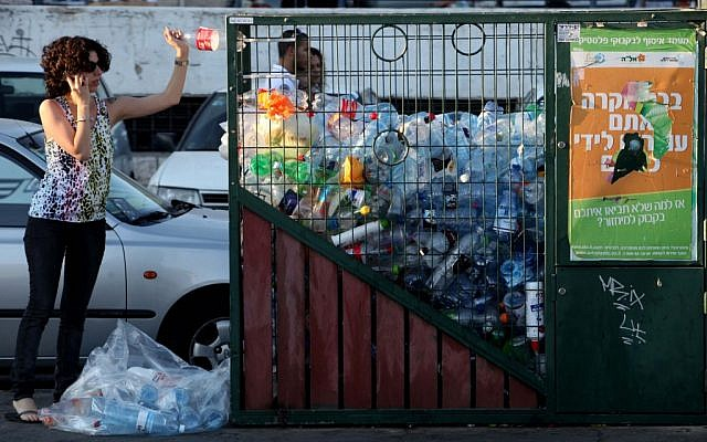A woman throws a bottle into the recycling bin in central Jerusalem. (photo credit: Nati Shohat/Flash90)