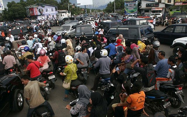 Indonesians stuck in a traffic jam as they flee to higher ground to escape a possible tsunami. (photo credit: AP/Heri Juanda)