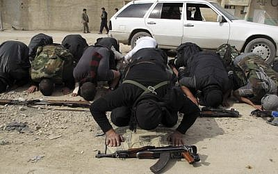 Free Syrian Army fighters perform the noon prayer in a neighborhood of Damascus, Syria (photo credit: AP)