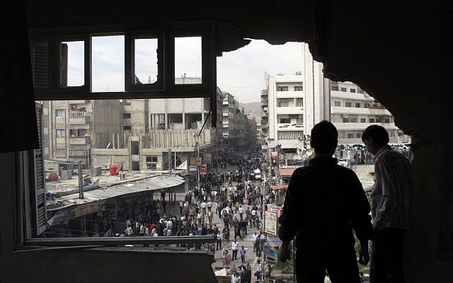 Syrian youth stand in a building damaged by tank shells in Damascus after a raid by Syrian troops killed several rebels and civilians last week (photo credit: AP)