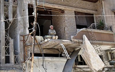 A man sits in his bombarded home in Homs April 22 (photo credit: AP)