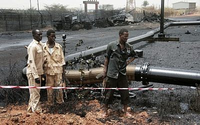 Sudanese armed forces stand near burnt oil pipes at the oil-rich border town of Heglig, Sudan. (photo credit: AP/Abd Raouf)