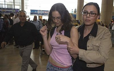 An activist is ushered away by security at Ben Gurion Airport on Sunday (photo credit: Dan Balilty/AP)