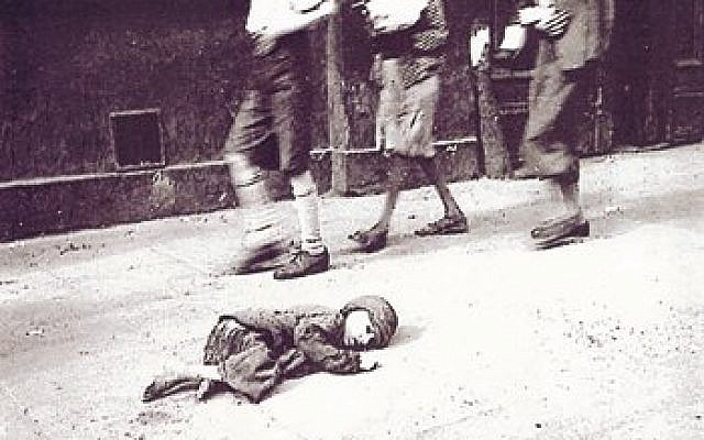 A child dying in the streets of the Warsaw Ghetto (photo credit: photo by Heinz Joest, a Wehrmacht sergeant, Wikimedia Commons)